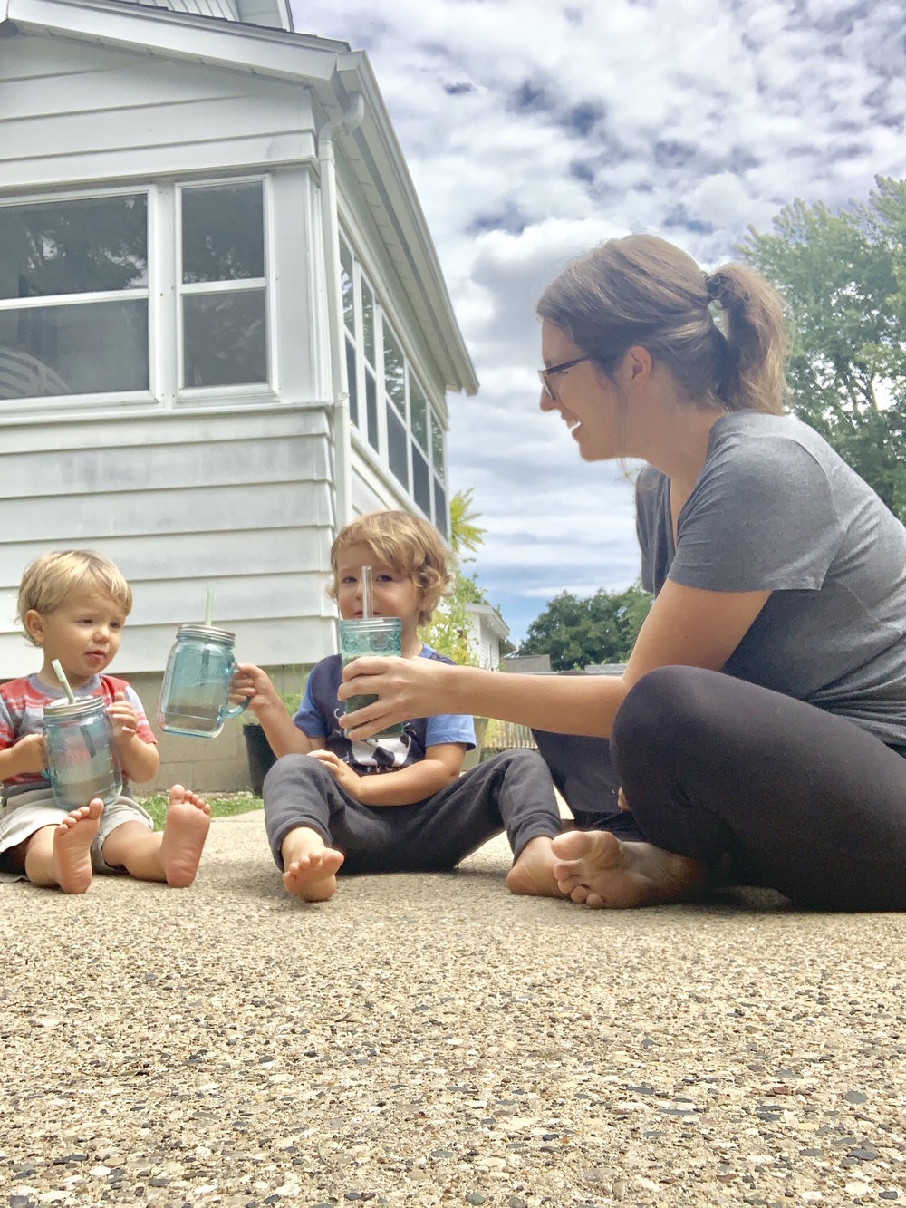 mom and two toddler boys sitting outside drinking shakes in teal cups