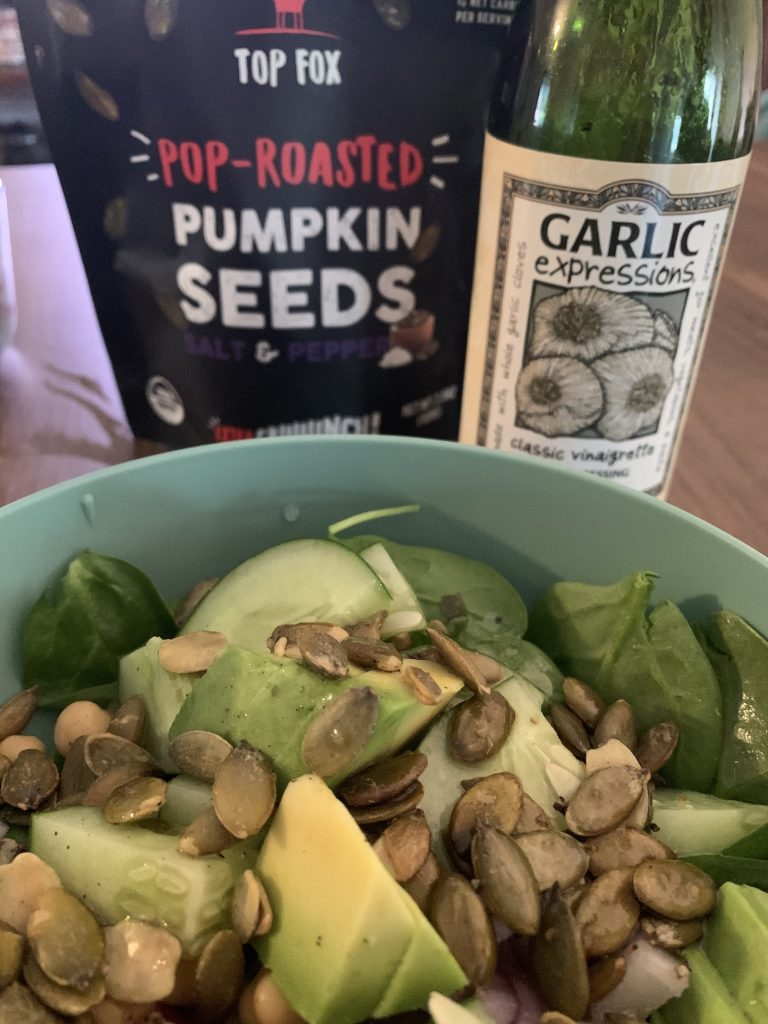 close up photo of a spinach salad topped with cucumber, avocado, and salt & pepper pop-roasted pumpkin seeds. Bag of pumpkin seeds and garlic expressions salad dressing in the background.