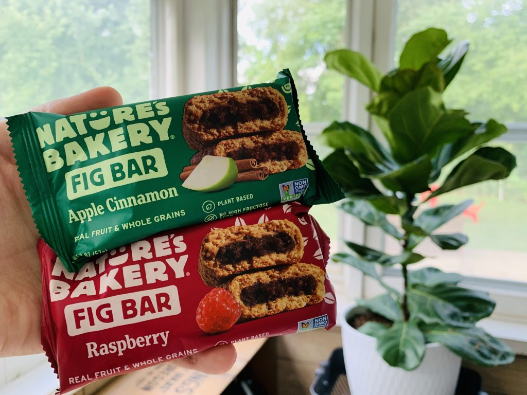 Two Natures Bakery fig bars being held in front of a green Fiddle Leaf Fig tree.
