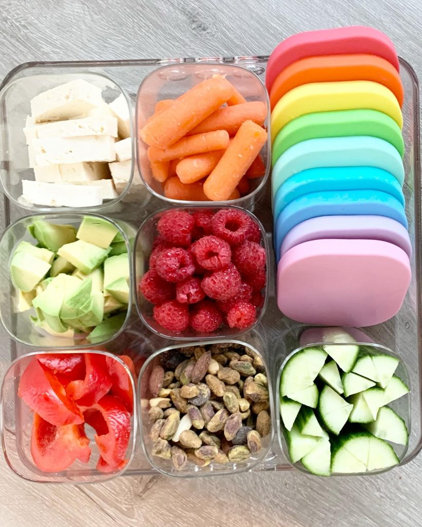 Square acrylic tray with 9 small cubes that contain fruits, vegetables, and nuts. The tray is on a gray counter and a variety of rainbow lids are shown.