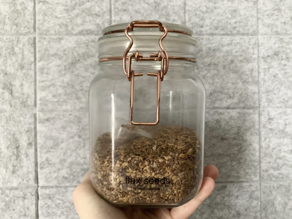 hemp seeds in a glass jar being held in front of a gray felt background.