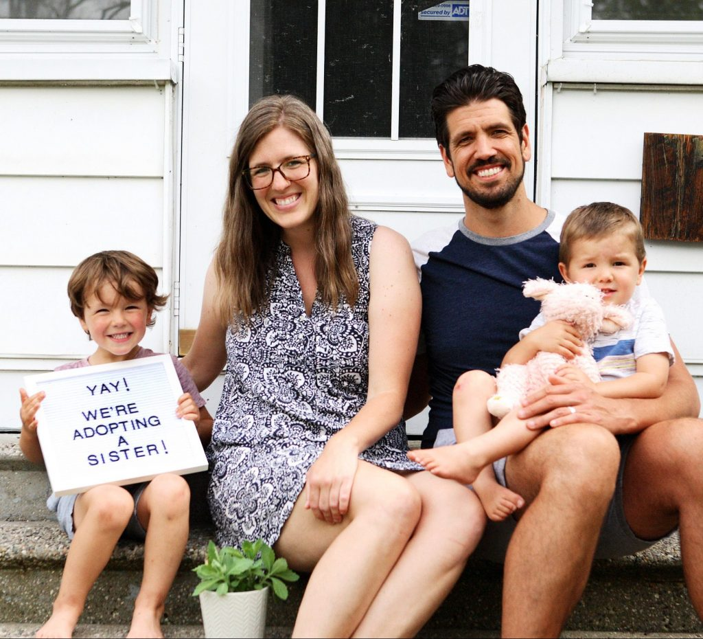 "Our family sitting on the front porch holding a sign that says ""YAY! We are adopting a sister!"""